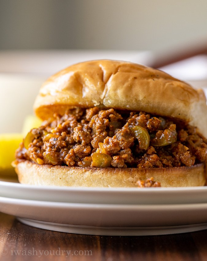 Piled high Sloppy Joe meat on toasted bun with dill pickle