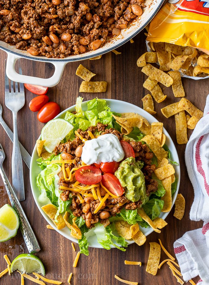 Plate full of taco salad with taco toppings.