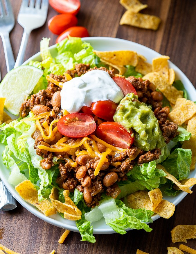 This Quick Taco Salad Recipe is filled with seasoned ground beef and pinto beans on top of corn chips and lettuce with all your favorite taco toppings. It's great for busy weeknights!