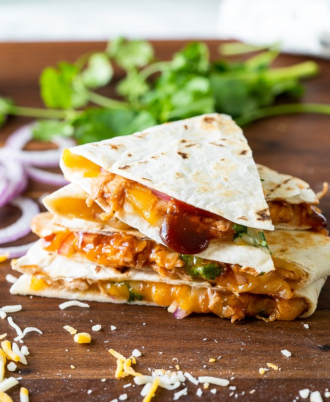 Sliced bbq chicken quesadilla on cutting board
