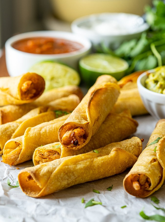 Plate full of crispy chicken taquitos