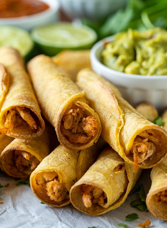 Stack of crispy baked chicken taquitos next to guacamole.