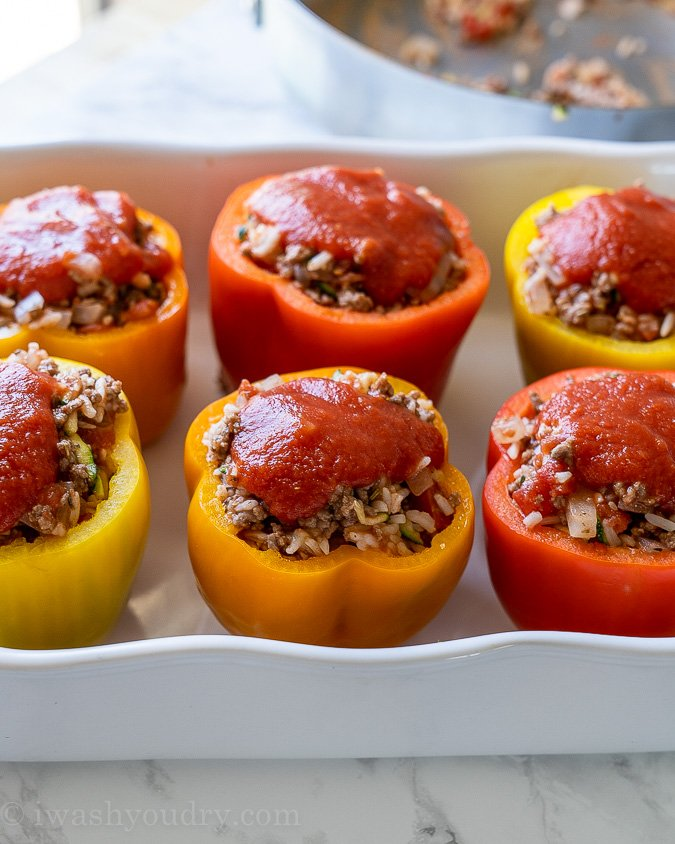 Tomato sauce on top of stuffed peppers