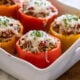 Casserole dish filled with cheesy stuffed peppers.