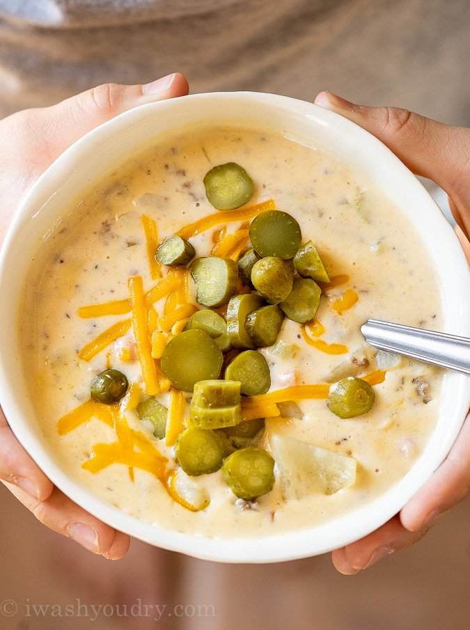 Bowl of Cheeseburger Soup being held in hands.