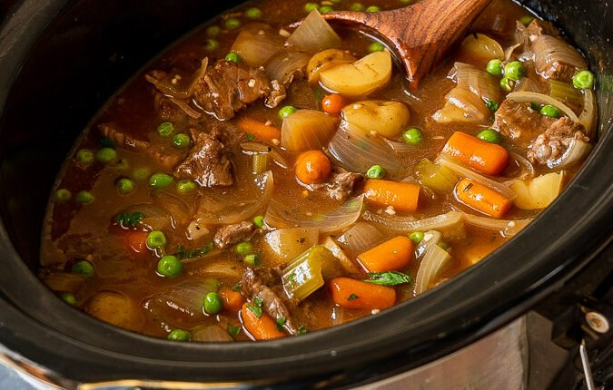 Beef stew in a slow cooker with wooden spoon