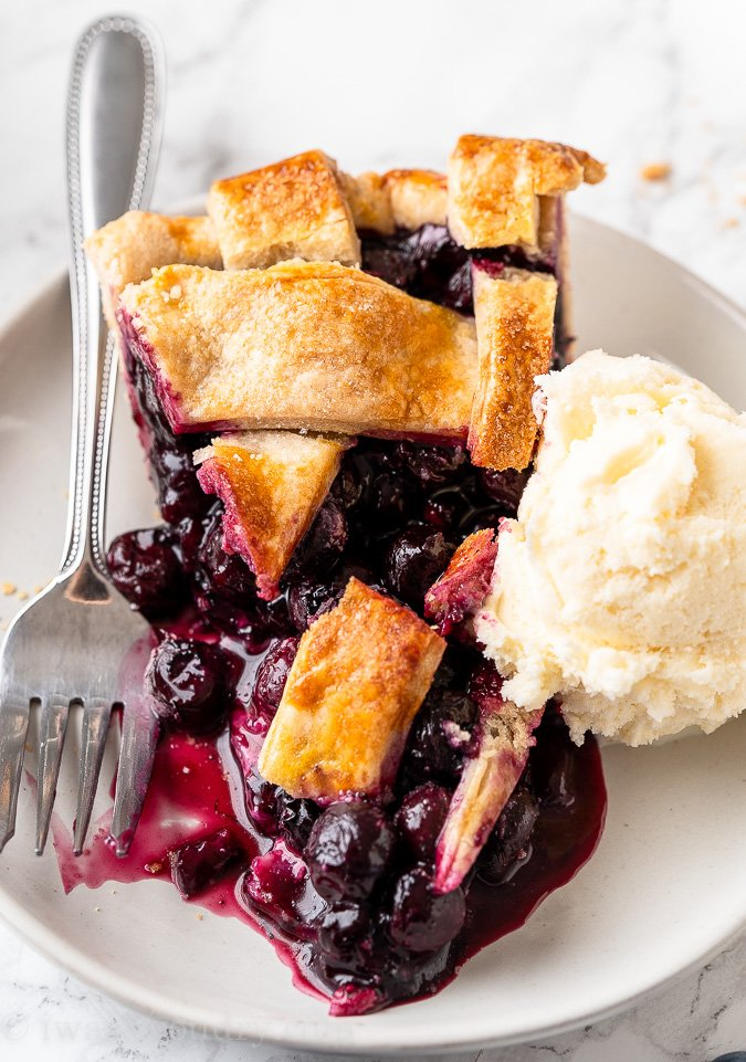 blueberry pie on plate with vanilla ice cream