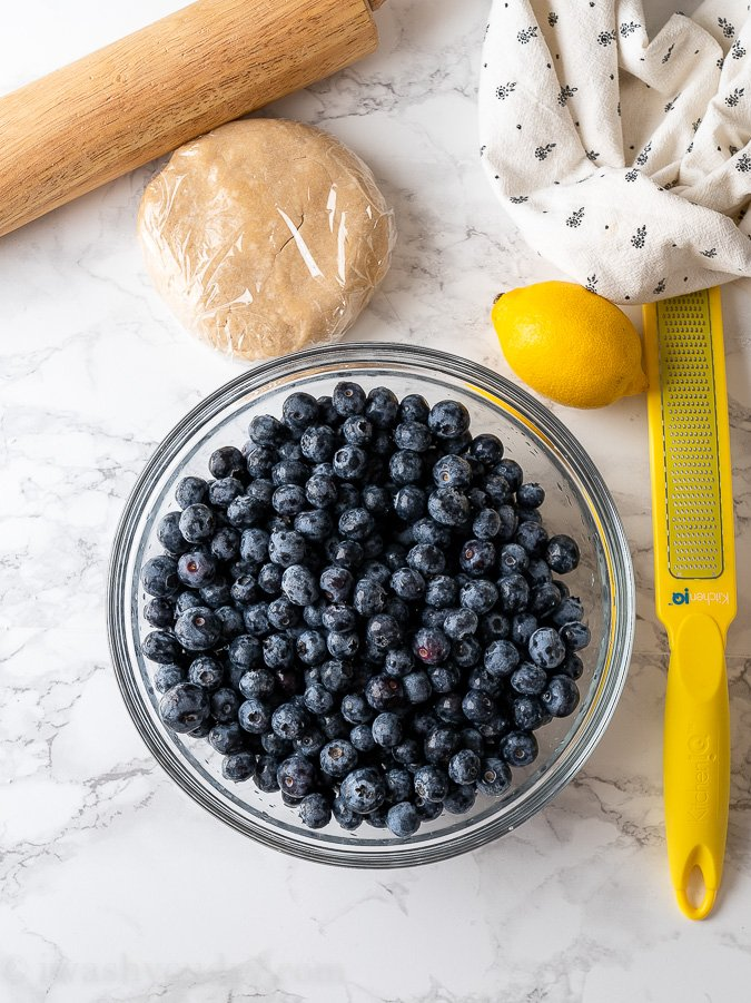 blueberries and lemon on cutting board