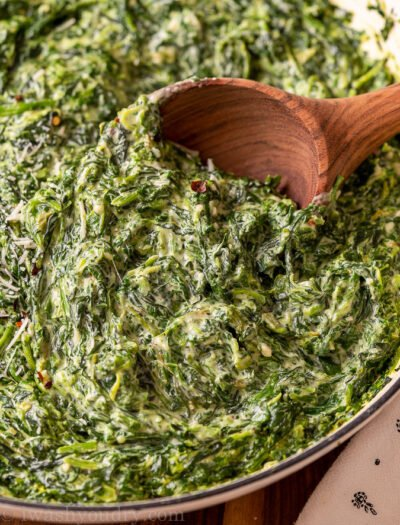 closeup of spinach in a pan with wooden spoon