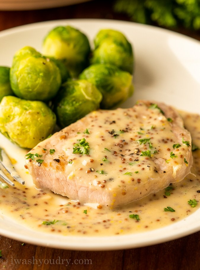 juicy pork chop on plate with mustard sauce