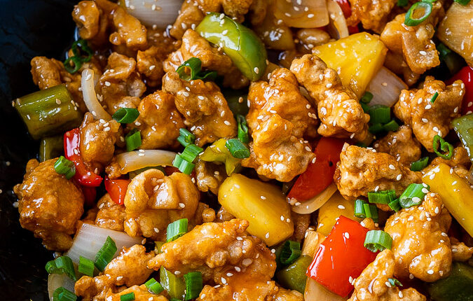 wok filled with sweet and sour chicken and vegetables