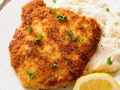 pork schnitzel on top of mashed potatoes with lemon wedge.