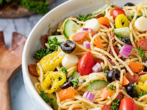 Blue bowl with spaghetti, tomatoes, cucumbers, peppers, olives, and italian dressing on marble table with wood spoon.