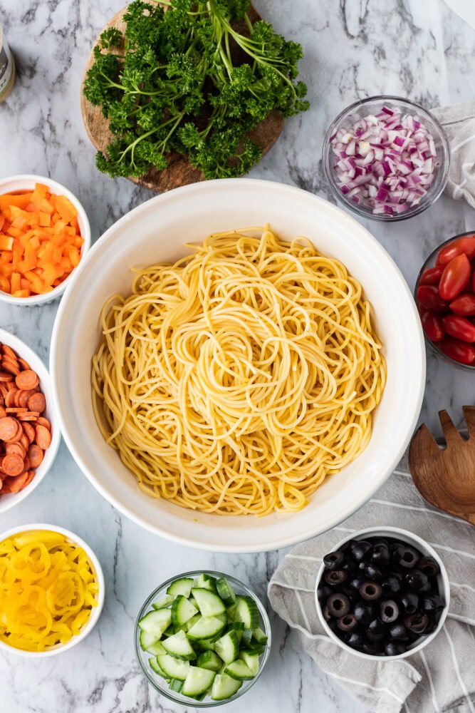 Bowl of Spaghetti noodles with bowls of veggies in a circle.