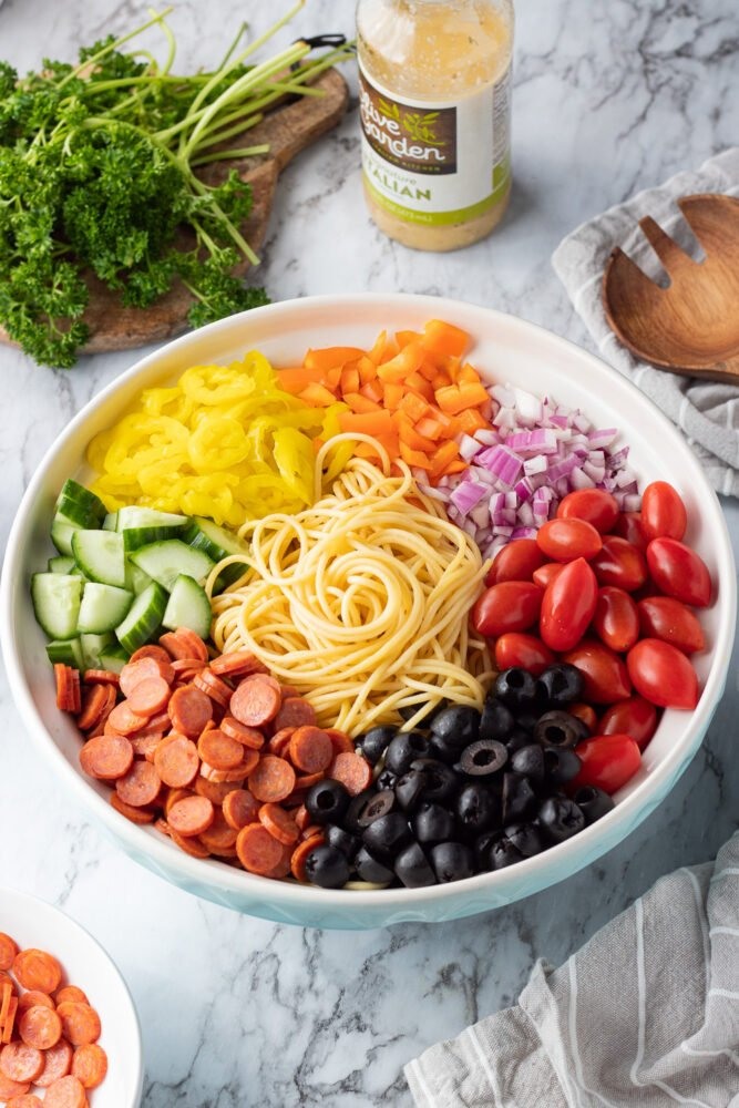 ingredients in a bowl for spaghetti pasta salad with parsley and italian dressing.