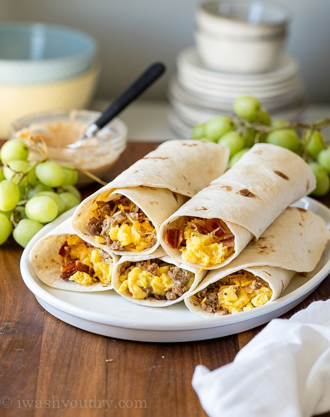Breakfast burritos on a plate with grapes and sauce on side.