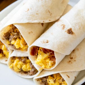 plate of breakfast burritos with bacon and sausage