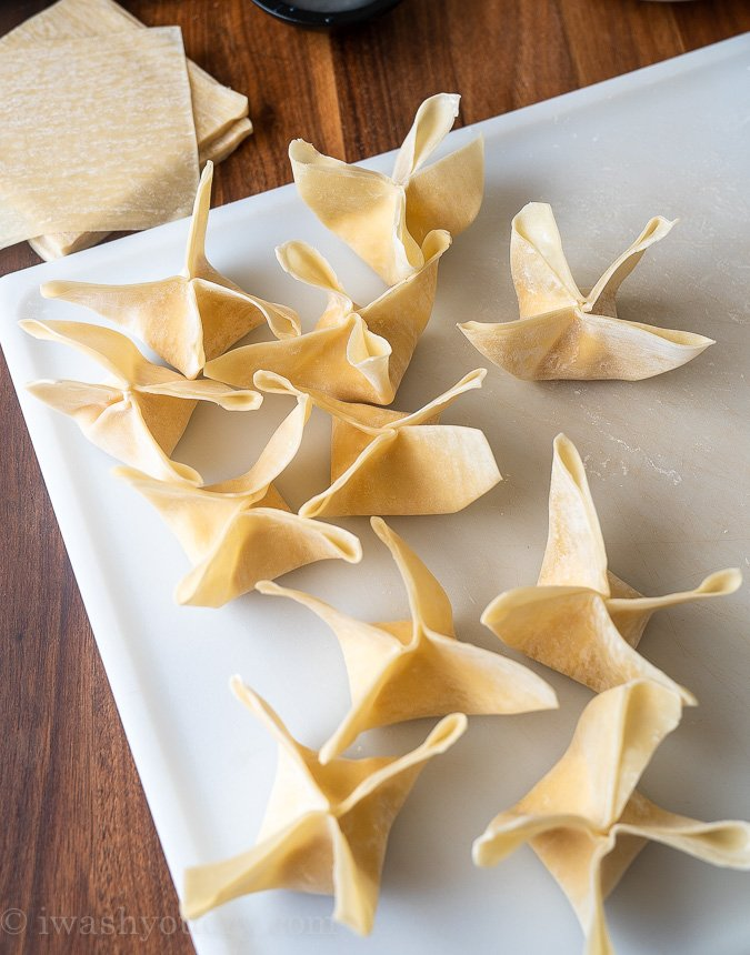 uncooked cream cheese wontons on white surface