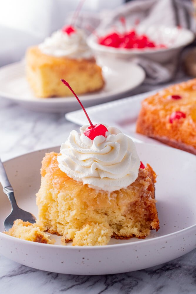 slice of pineapple upside down cake on white plate with fork and whipped cram.