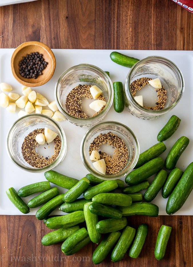 preparing mason jars with spices and cucumbers