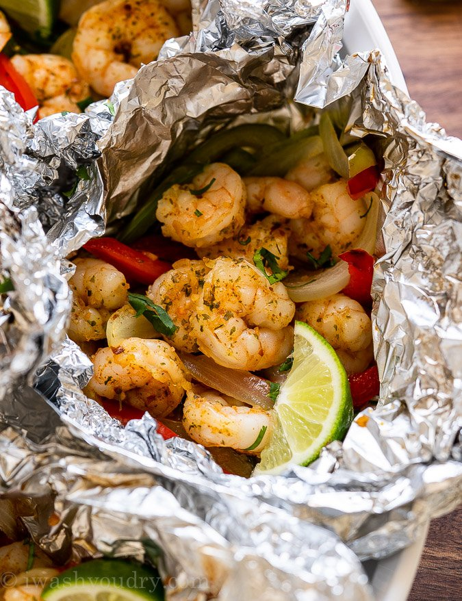 shrimp fajitas in foil packet with limes and peppers
