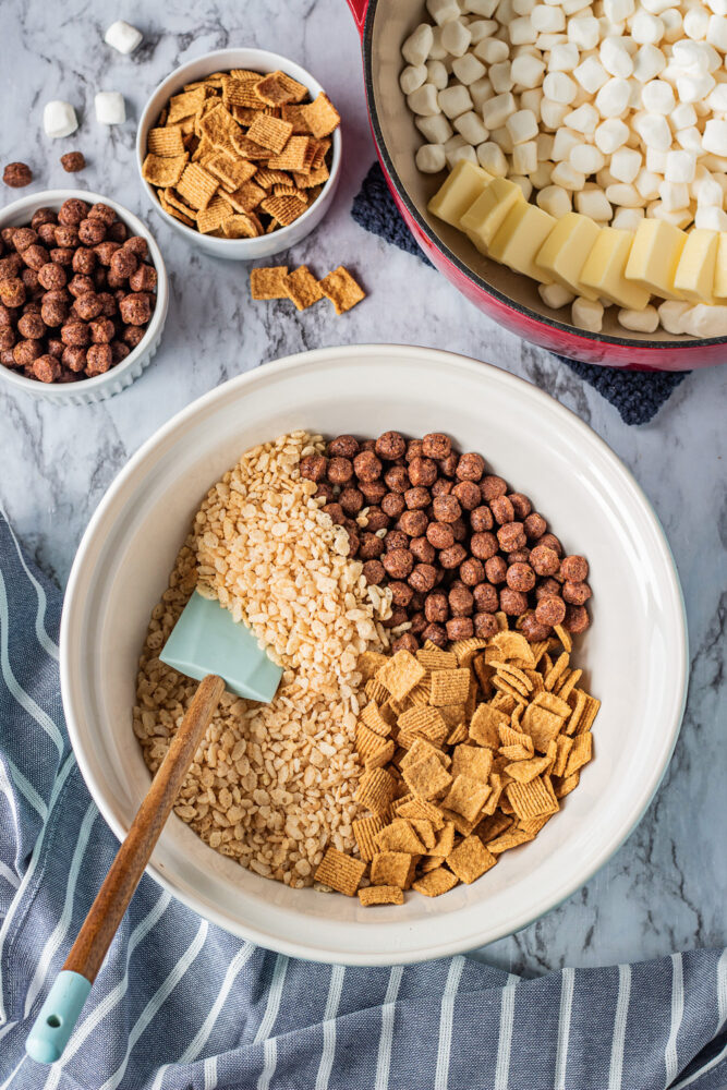 ingredients for s'mores rice krispie treats in a white bowl with blue spatula.