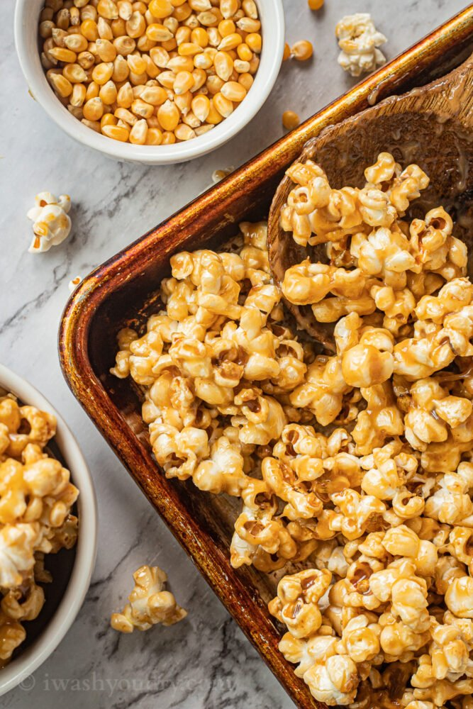 caramel corn in metal pan with spoon and popcorn kernels in white bowl