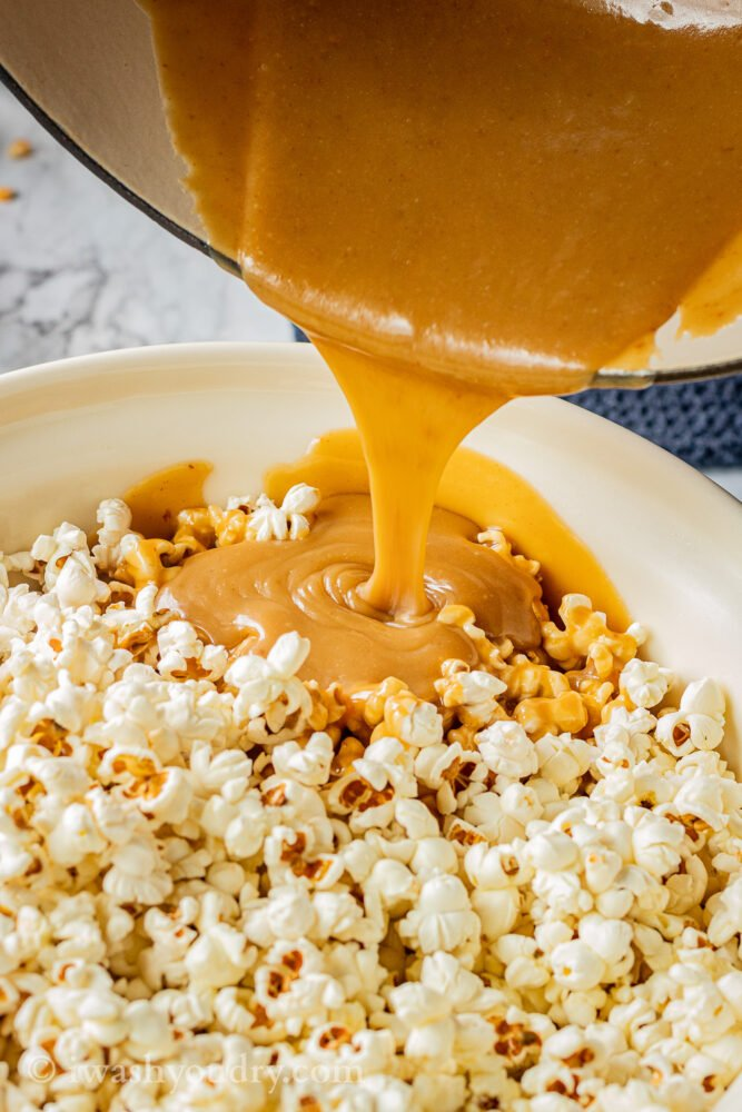 pouring caramel into bowl of popped popcorn