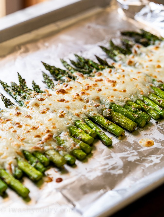 mozzarella cheese melted over asparagus in pan