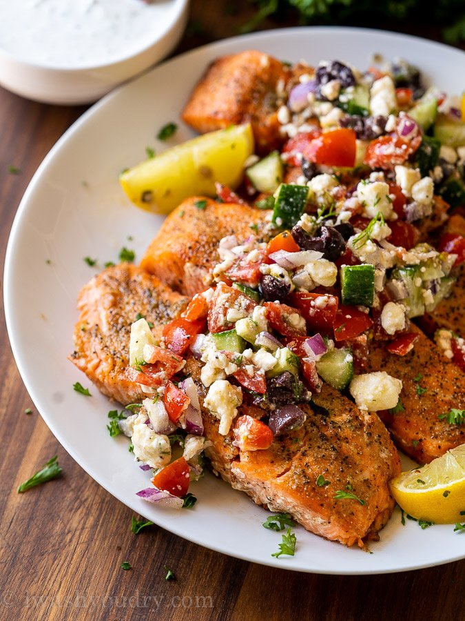 grilled salmon on white plate with greek salsa