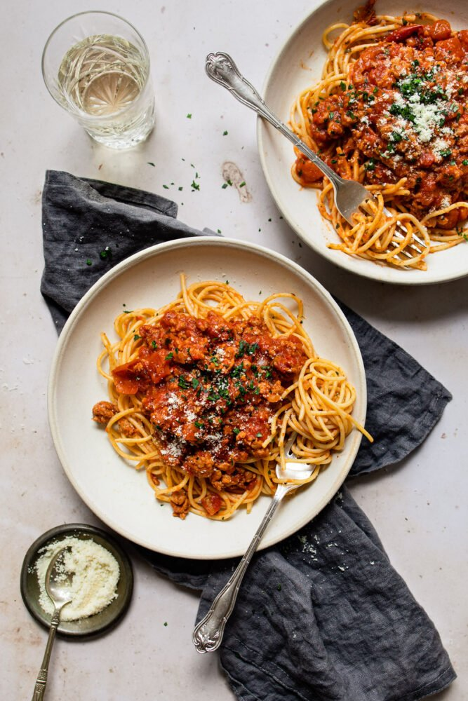 two plates of pasta with forks