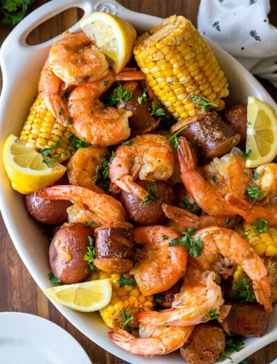 white dish filled with shrimp, potatoes, corn and sausage