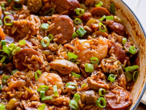 white pan filled with jambalaya with rice and green onions