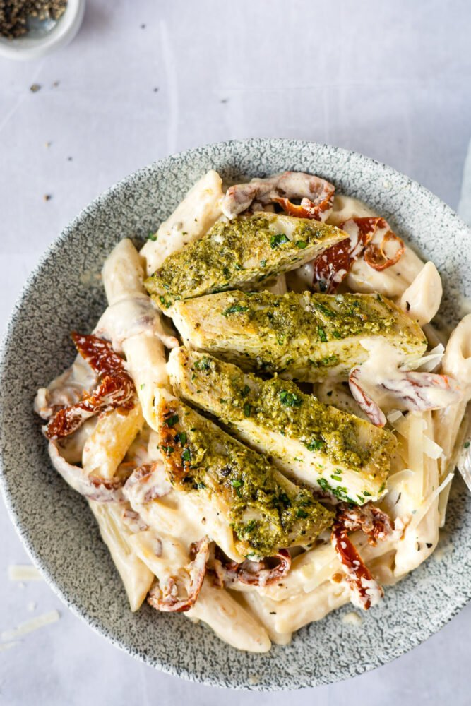 plate of creamy penne pasta with sliced chicken on top