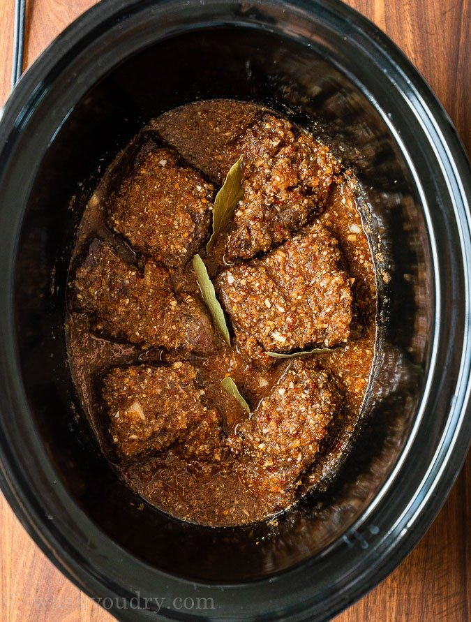 chuck roast in slow cooker with sauce on top