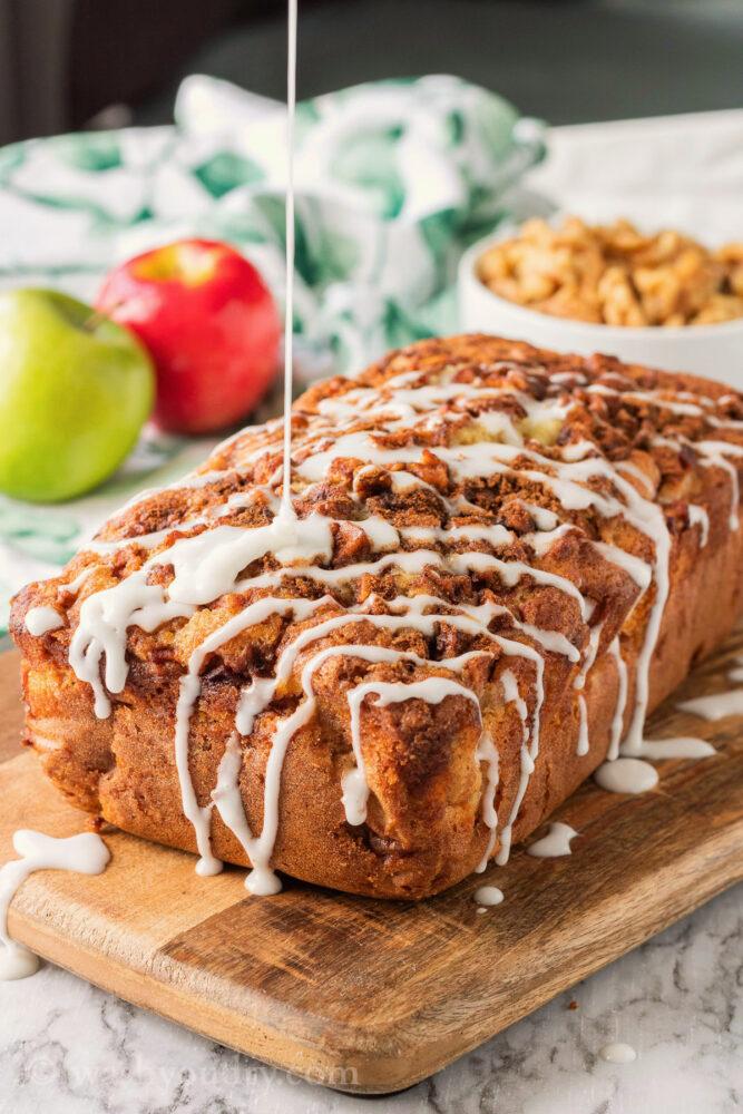 Vanilla glaze on baked amish apple fritter bread on wood cutting board.