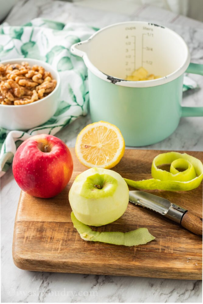 Apples and lemon on wood cutting board with bowl of walnuts and measuring cup of apples.
