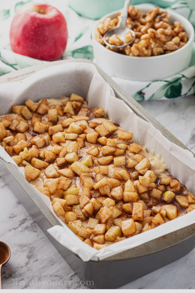 Chopped apples on amish apple fritter batter in metal pan.
