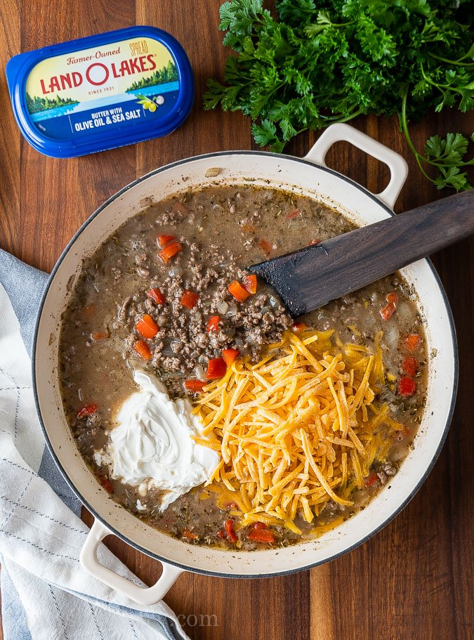 ground beef mixture with sour cream and cheese in pan with wooden spoon