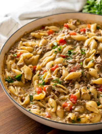 white pan full of ground beef and pasta shells in a creamy sauce